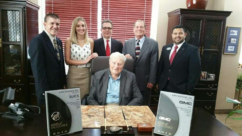 """(Standing from left to right) Buick GMC South Central Zone Manager Steve Kuhl, Finance Director Lauren Wiesner, General Manager Terry Hatfield, Dealer Don Wiesner and Buick GMC Houston District Manager Eric Macias circle around J.W. Wiesner with the dealership's GMC """"Mark of Excellence"""" awards from 2013 and 2014."""