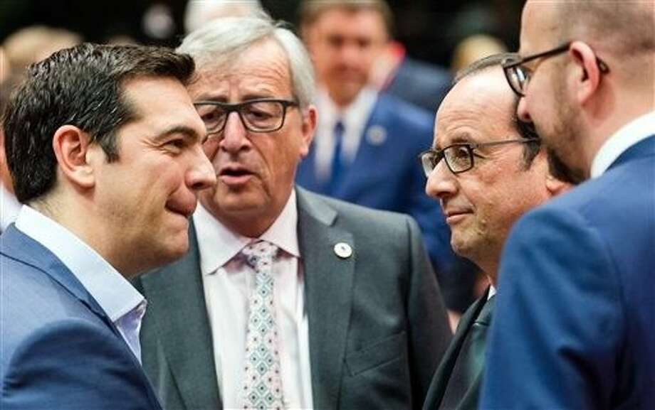 Greek Prime Minister Alexis Tsipras, left, speaks with, from left, European Commission President Jean-Claude Juncker, French President Francois Hollande and Belgian Prime Minister Charles Michel during a meeting of eurozone heads of state at the EU Council building in Brussels on Sunday. Skeptical European creditors raced Sunday to narrow differences both among themselves and with Athens, aiming to come up with a tentative agreement to stave off an immediate financial collapse in Greece that would reverberate across the continent. Photo: Geert Vanden Wijngaert