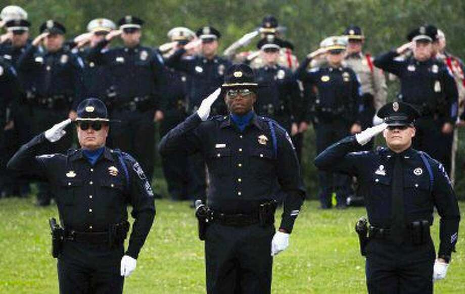 Conroe police officers salute during the annual Police Officers Memorial Ceremony at Heritage Place Park on Thursday. The ceremony coincided with National Police Week where communities across the country remember those officers who have lost their lives in service to their communities.
