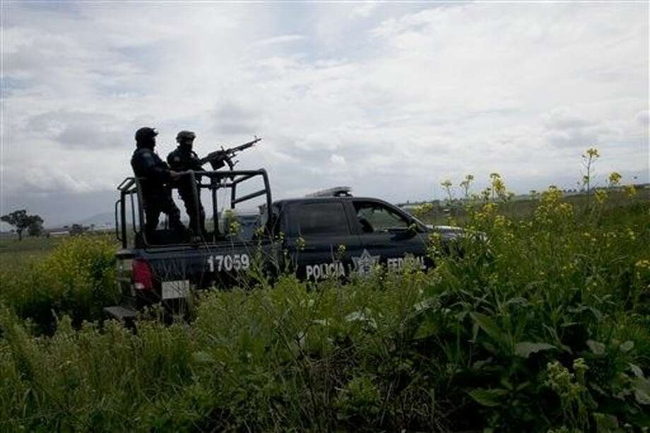 "Mexican federal police guard near the Altiplano maximum security prison in Almoloya, west of Mexico City, Sunday. Mexico's most powerful drug lord, Joaquin ""El Chapo"" Guzman, escaped from a maximum security prison through a tunnel that opened into the shower area of his cell, the country's top security official announced. Photo: Marco Ugarte"