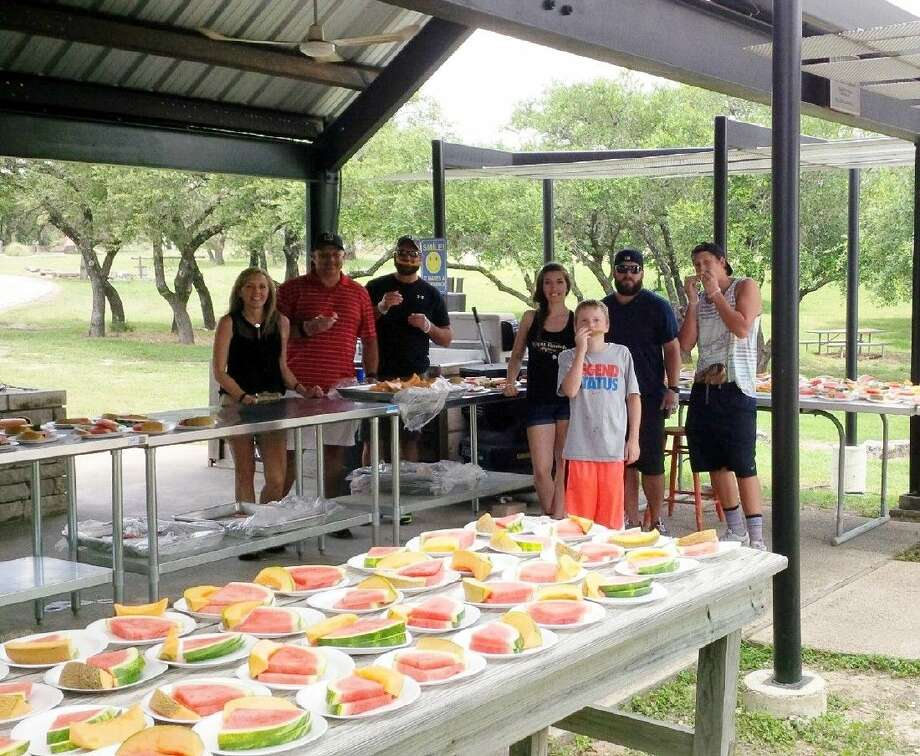 """Last week, the Conroe Noon Lions Club sponsored a """"Melon Fest"""" at the Texas Lions Camp in Kerrville. Pictured (left to right) are Sharene Carr, Scott Petty, Mark Curlee, Erika Cummings, Josh Cummings, Cole Curlee and, front, Matthew Curlee."""