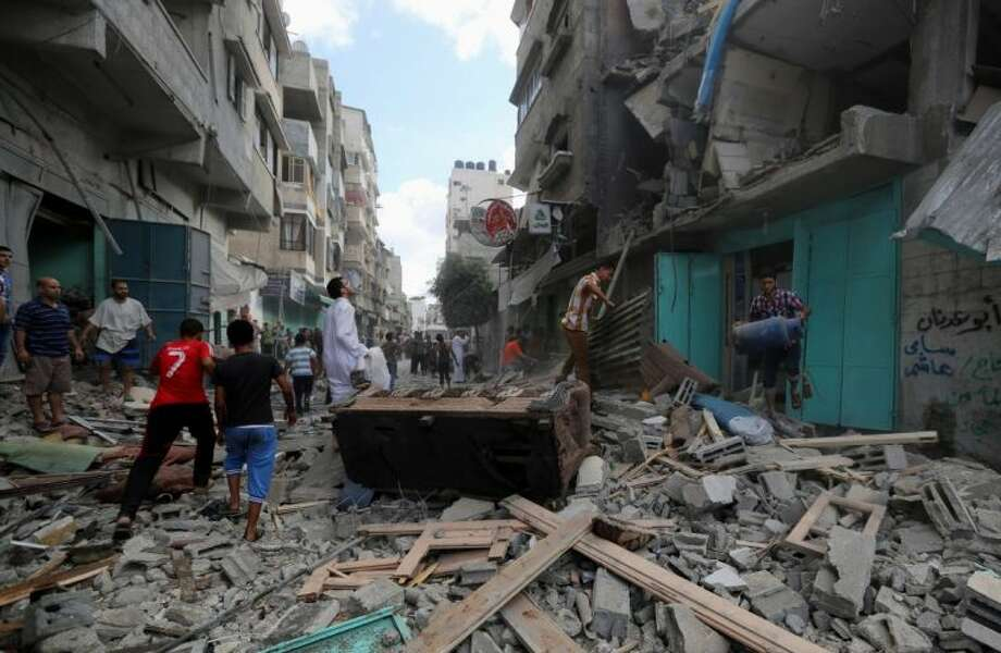 Palestinians inspect the rubble of a building to pick up their usable belongings after it was hit by an Israeli missile strike in Gaza City, Friday, July 18, 2014. Israeli troops pushed deeper into Gaza on Friday to destroy rocket launching sites and tunnels, firing volleys of tank shells and clashing with Palestinian fighters in a high-stakes ground offensive meant to weaken the enclave's Hamas rulers. Photo: Hatem Moussa