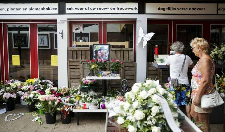 Women stand near to a portrait of Neeltje Tol, left, and Cor Schilder, right, placed with flowers and candles in front of their flower shop in Volendam, Netherlands, Saturday, July 19, 2014. An attack on a Malaysian jetliner shot down over Ukraine on Thursday killed 298 people from nearly a dozen nations, more than half being Dutch. Tol and Schilder were among those killed. Photo: Phil Nijhuis