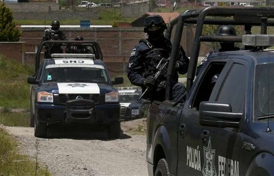 """Federal Police stand guard near a half-built house near the Altiplano maximum security prison in Almoloya, west of Mexico City, Monday. A widespread manhunt that included highway checkpoints, stepped up border security and closure of an international airport failed to turn up any trace of Mexican drug kingpin Joaquin """"El Chapo"""" Guzman by Monday, more than 24 hours after he escaped through an underground tunnel leading from his Altiplano prison cell's shower area. Photo: Marco Ugarte"""