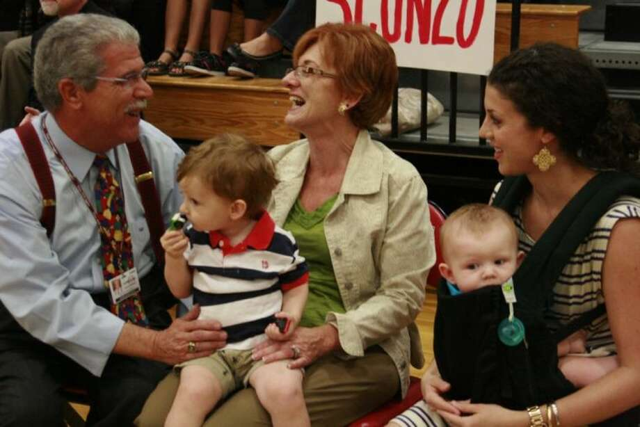 Humble ISD Superintendent Dr. Guy Sconzo, left, shares a laugh with his family - wife, Diane; daughter, Jennifer; and his two grandchildren Noah and Benjamin at a surprise pep rally in his honor Sept. 25, 2013.