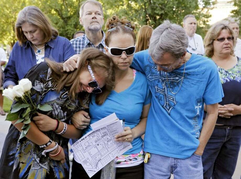 In this July 20, 2013 file photo, Jasmine Christman, left, is comforted by her mother Yulanda Vega Jordan, center, and father Jack Jordan during a memorial service for those killed in the Aurora theatre killings, in Aurora, Colo. Two years have passed since a man wearing police-style armor killed 12 and wounded 70 during a midnight movie screening. For many of the survivors, the trauma is still fresh. Photo: Ed Andrieski