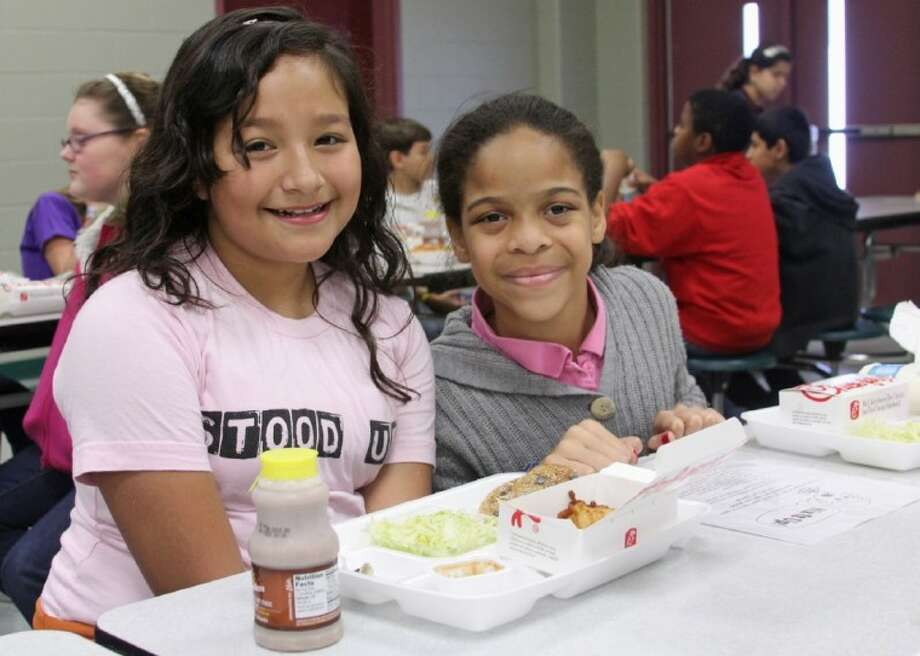 "Sablatura Middle School students Arissa Contreras (left) and Stasha Adams participate in a ""Mix It Up at Lunch"" activity organized by the school's student council. Photo: Pearland ISD"