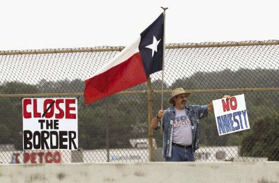 "A protester holds a Texas flag and sign that says ""No Amnesty"" during a protest against illegal immigrants Saturday in Conroe. The national debate, which originally surrounded the question of how to fix the United States' immigration system and provide a path to citizenship for millions of illegal immigrants, has turned into a growing outcry over the border. Go to HCNpics.com to view more photos from the demonstration. Photo: Jason Fochtman / Conroe Courier"