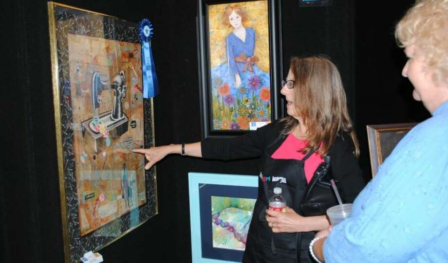 Lone Star Art Guild Judge Enid Wood points out the details of the Mixed Media piece created by Woodlands Art League member Linda Jackson (right) at Saturday's Lone Star Art Guild 52nd Annual Convention.