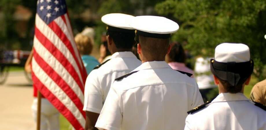 Navy ROTC cadets from Rice University stand at attention as the tribute caisson passes. Photo: Rusty Graham