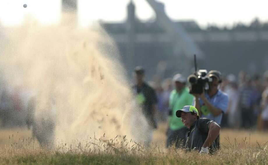 Rory McIlroy of Northern Ireland plays a shot out of a bunker on the 16th hole during the British Open. McIlroy turned in a second-round 66 on Friday. Photo: Scott Heppell