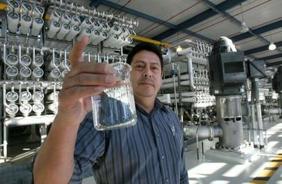 In this 2010 photo, Art Ruiz shows samples of water at the Kay Bailey Hutchison Desalination Plant in El Paso, Texas. Texas lawmakers will tour desalination plants across the state as they study ways to address water shortages expected to worsen in the coming decades. Photo: Victor Calzada / El Paso Times