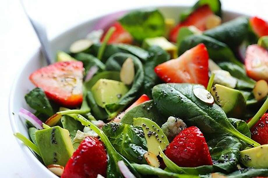 Greens with fruits make for a refreshing spring salad. This salad has nuts, strawberries and spinach.
