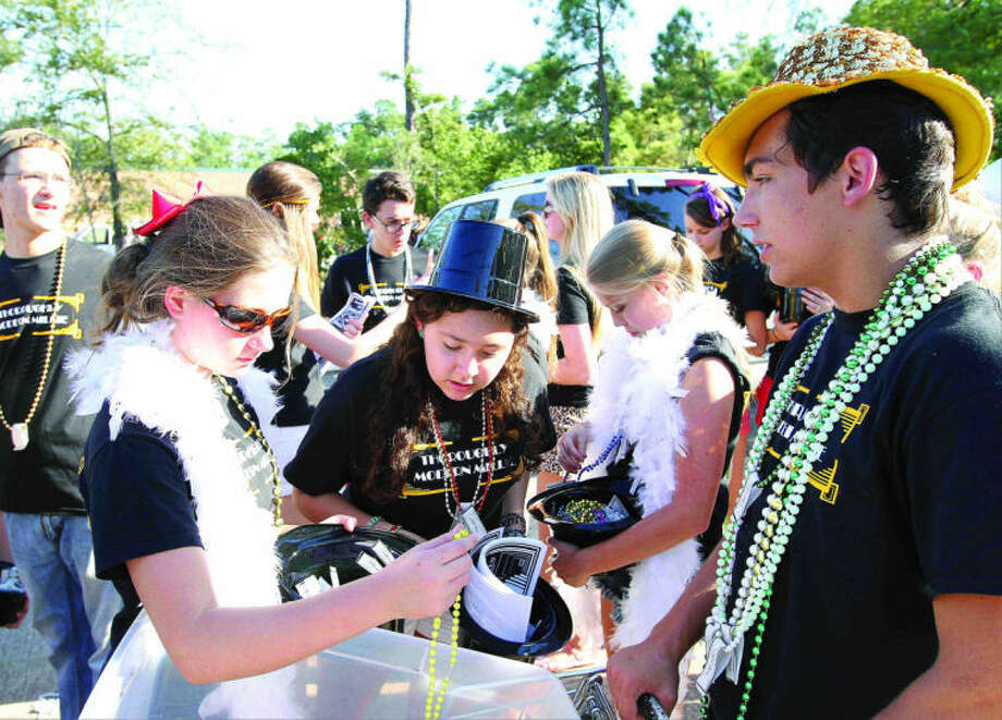 Members of The Woodlands High School acting club grab beads before the school's homecoming parade Wednesday. Go to HCNPics.com to view and purchase this photo, and others like it. Photo: Staff Photo By Jason Fochtman