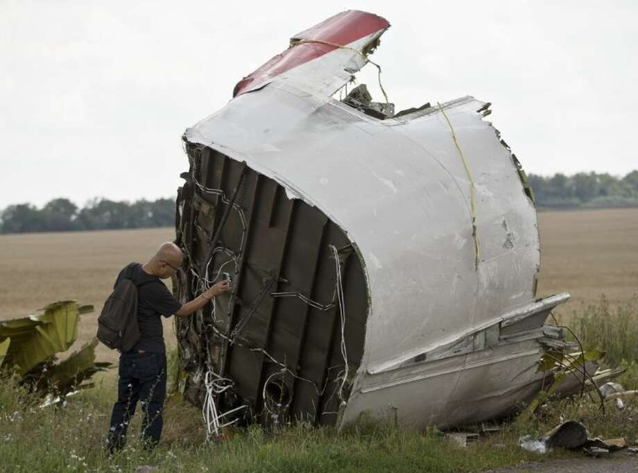 A Malaysian air crash investigator takes pictures of wreckage at the crash site of Malaysia Airlines Flight 17 near the village of Hrabove, eastern Ukraine, Tuesday.