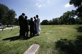 A family gathers in prayer as they visit a family member buried in the Islamic Garden at Restland Cemetery Friday in Dallas. A proposal to bring a Muslim cemetery to Farmersville has stoked fears among residents who are vehemently trying to convince community leaders to block the project.