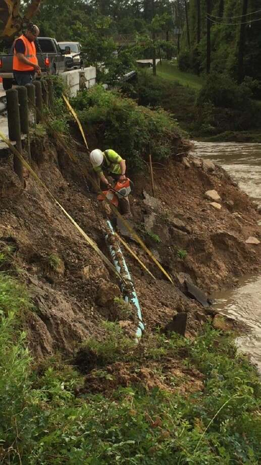 Crews with the Montgomery County WCID No. 1 worked Thursday after floodwaters caused damage to the bridge over Panther Branch on Sawdust Road.