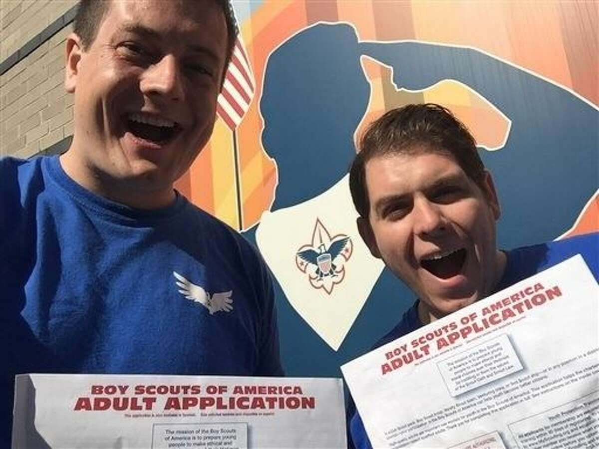 Eric Hetland, he, left, and Chris Zelis, fellow Scouts For Equality - Chicago chapter lead, hold up their applications for assistant scoutmasters before submitting them in the Chicago suburb of Oak Park.