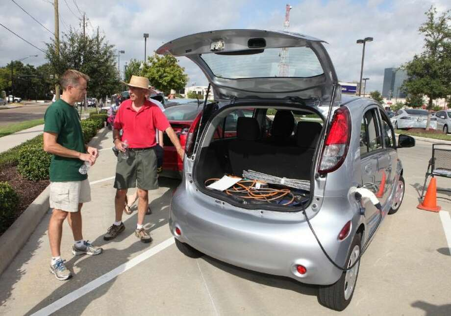 Joe Lengfellner of the Sierra Club looks at a Mitsubishi i-MiEV owned by Steve Hanrahan at the National Plug In Day in Houston at the eVgo Freedom Station on Saturday, Sept. 28. Photo: Photo By Alan Warren