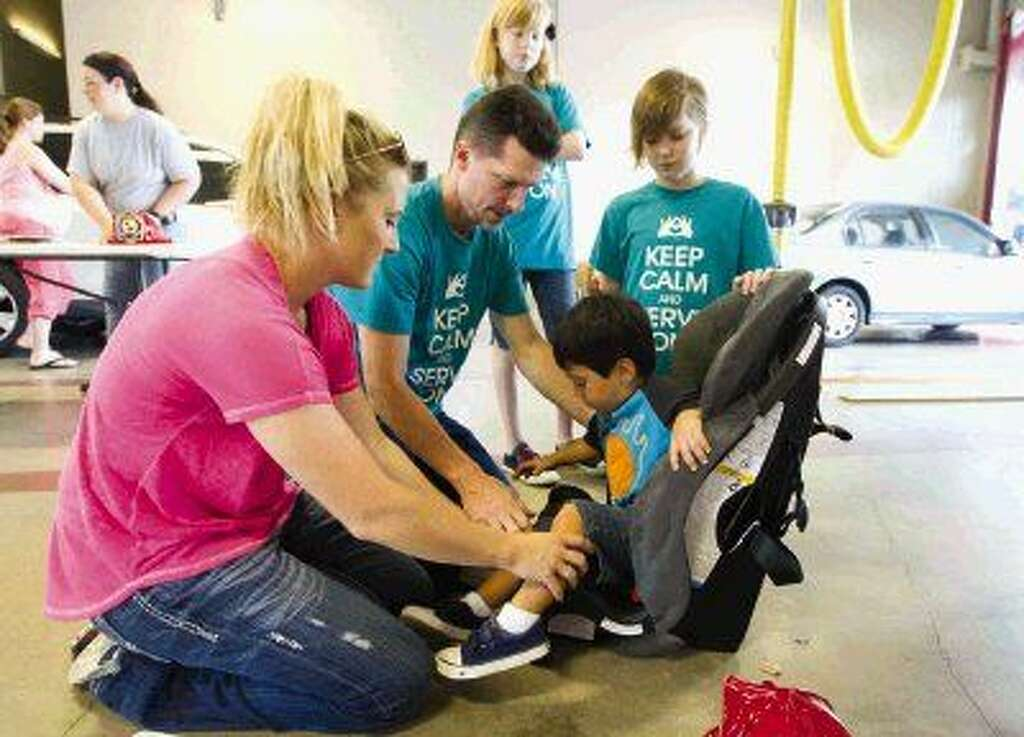 amy moser left helps arlie fry fit ryder yates in a car seat as volunteers with the safe kids
