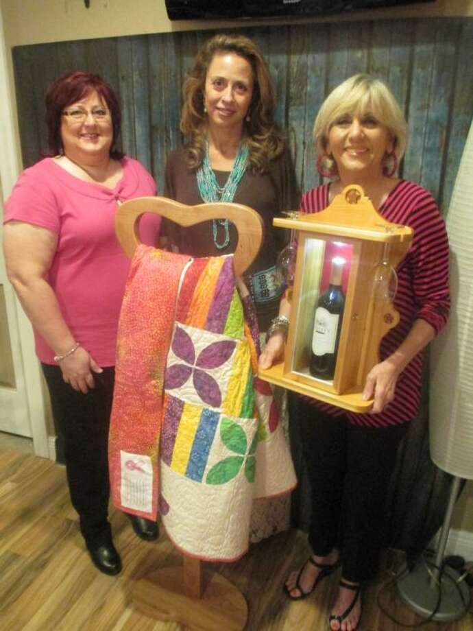 Jodie Robinson, owner of the boutique (center) admires two handmade raffle items - a handmade, decorative, modern brightly-colored appliqué and pieced quilt created and donated by Robin Ardoin (left), speech pathologist at Memorial Hermann Northeast Hospital, as well as a hand carved, lighted wooden wine case complete with wine glasses and a bottle of Texas-raised red wine. The case, donated by Memorial Hermann Northeast Volunteer Coordinator Nancy Allen is held by Raffle Chair Rose Marie Hartley and includes the Texas Lonestar carved in the top of the case.