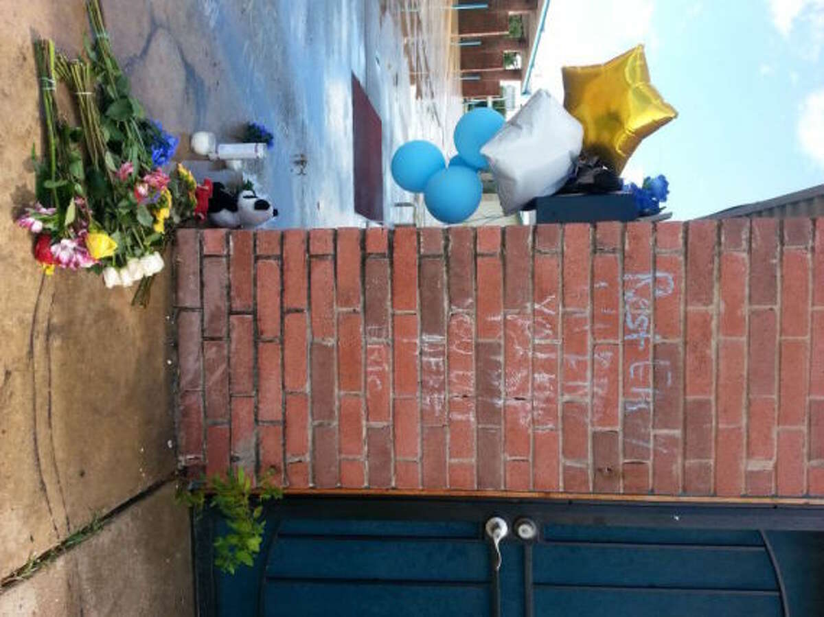 A shrine to the fallen on the side of Royal Wash Mobile Detailing & Car Wash's detailing facility, where three people were shot and killed Sunday, Sept. 29 on Avenue E near Murphy Road in Stafford.