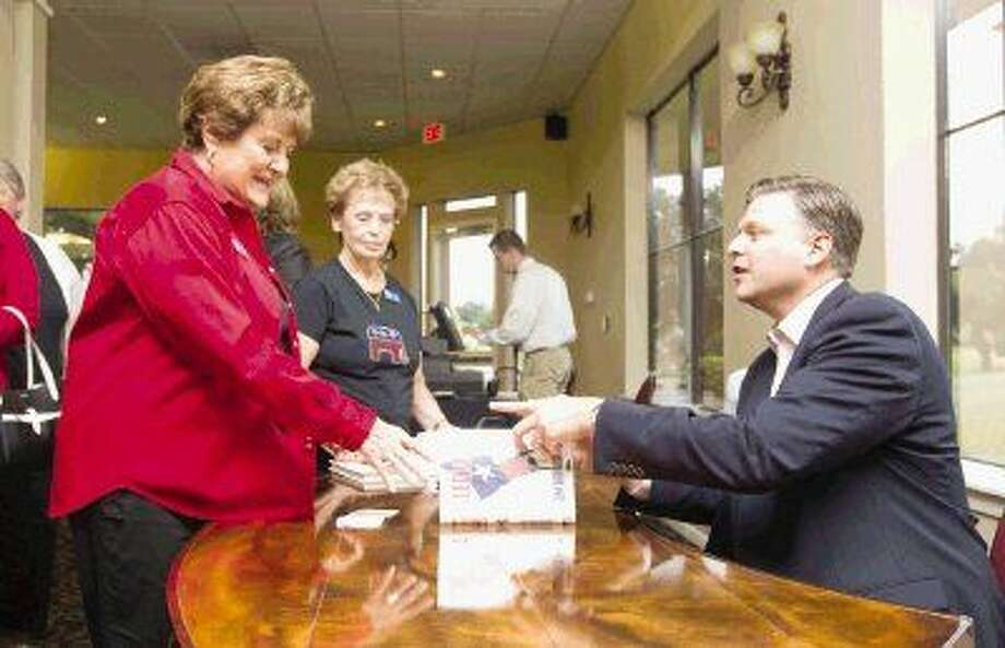 """Nan McShan, left, gets a copy of """"Allegiance"""" signed by KTRK Channel 13 news anchor and author Tom Abrahams after the Lake Conroe Area Republican Women meeting Thursday."""