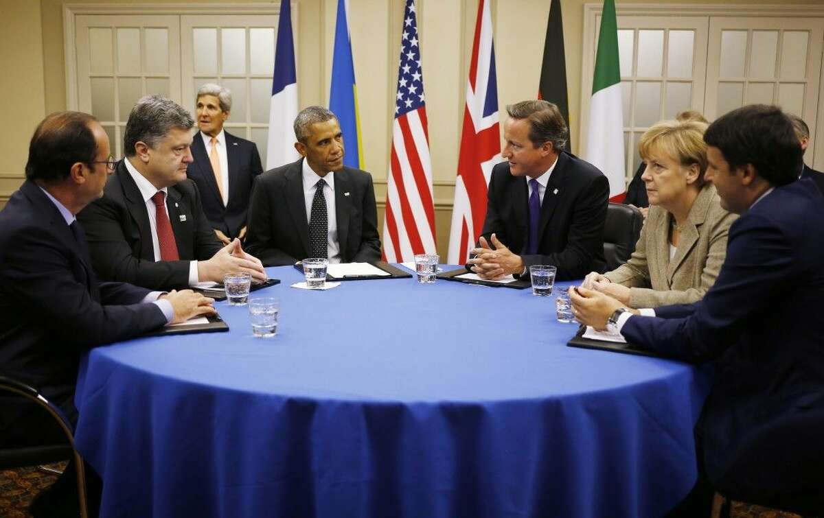 U.S. President Barack Obama, fourth from left, is seated at a table with, from left to right: France's President Francois Hollande; Ukraine President Petro Poroshenko; British Prime Minister David Cameron; German Chancellor Angela Merkel; and Italian Prime Minister Matteo Renzi as they meet about Ukraine at the NATO summit at Celtic Manor in Newport, Wales, Thursday, Sept. 4, 2014. U.S. Secretary of State John Kerry is seated at rear left.