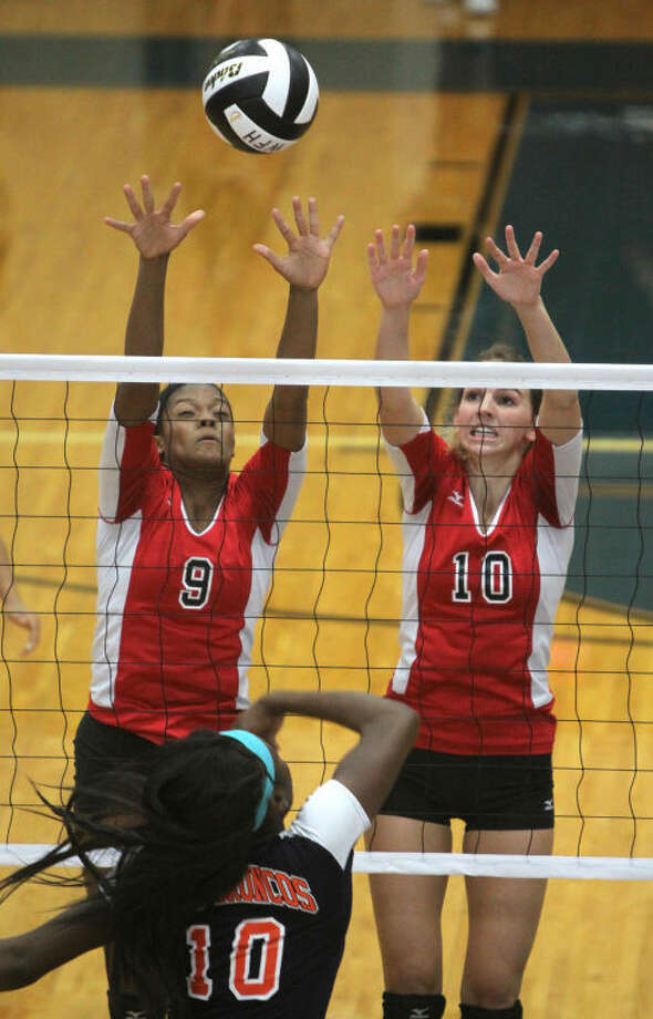 Austin's Cristen Coryatt and Erin Mulcahey try to block Bush's Olubunmi Okunade during a District 23-5A volleyball match Oct. 1 at Wheeler Field House in Sugar Land. The Lady Bulldogs won in three sets to improve to 6-0. Visit www.HCNPics.com for more photos.