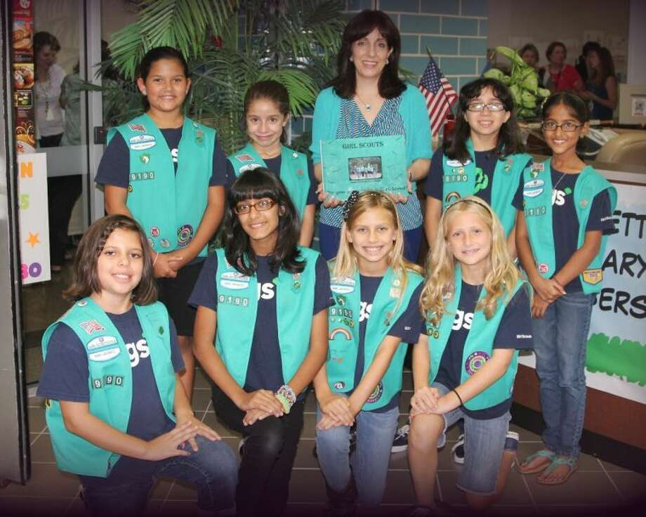 Shown following the book presentation at Settlers Way Elementary School are Junior Girl Scout Troop 19190 members (front row, from left): Abby R., Alishba N., Hayley W., Megan M.; and (back row) Emily C., JoAnn V., Tracy Sackllah, SWE librarian; Sofia V., and Ayushi O.