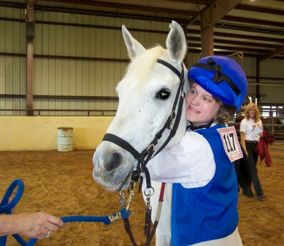 SIRE horse rider Gabby Powers hugs Scotter Girl the horse, one of several therapeutic horses which helps people with disabilities. SIRE recently received a donation of $10,000 from PetSmart.