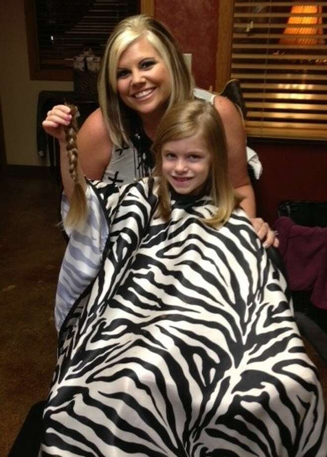 Evie Ragas, 6, of Spring, decided on her own to cut her hair and donate it to Pantene Beautiful Lengths, a non-profit that has donated 24,000 free real-hair wigs to the American Cancer Society's wig banks, which distribute wigs to cancer patients across the country. Also pictured is Kelly Drebert, of Total Image in Salons Of The Woodlands, who cut her hair.