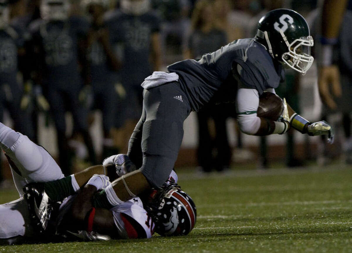 Spring's Xavier Jones (5) is tackled close to the line of scriammage by Paul LeBlanc (10) of Westfield at Leonard George Stadium on Friday, Oct. 11, 2013, in Spring. ( Joe Buvid / For Houston Community Newspapers )