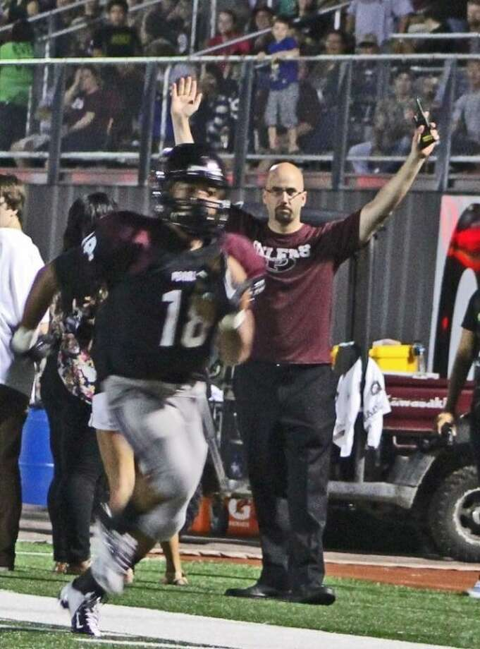 Pearland's Jacoby Lewis runs for a touchdown Friday night in Pearland's 62-0 homecoming win over Pasadena Rayburn while Pearland High School principal Larry Berger anticipates the score.