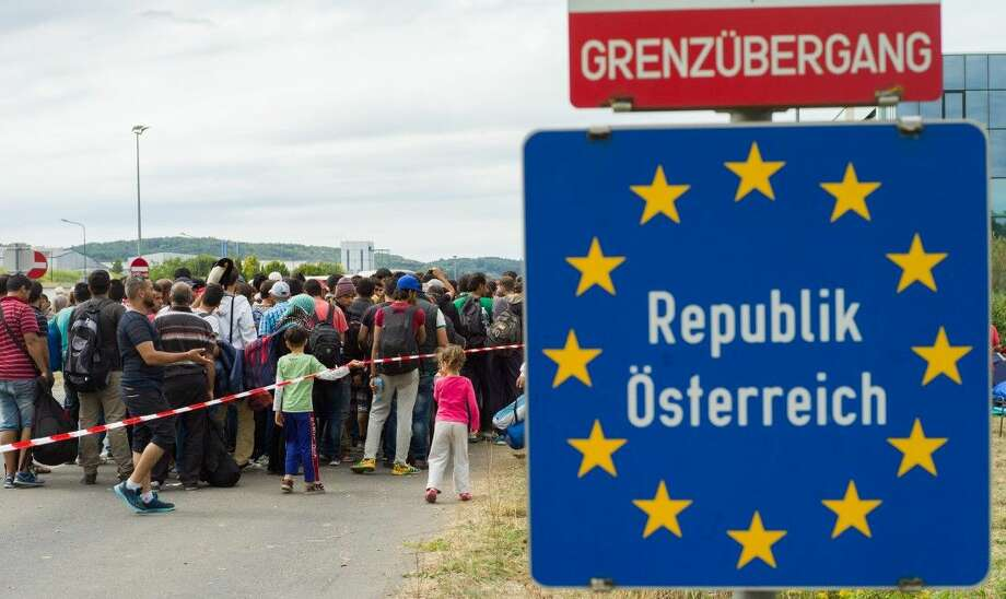 Migrants queue up for buses after they arrived at the border between Austria and Hungary near Heiligenkreuz on Saturday. Photo: Christian Bruna