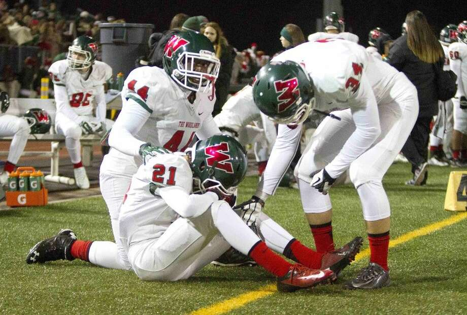 The Woodlands linebacker Kameron Gladney, left, and defensive back Dustin Baranowski comfort defensive back David Lopez after the Highlanders' 38-20 loss to Klein Oak in the Class 6A bi-district playoffs on Friday at Klein Memorial Stadium. To view or purchase this photo and others like it, visit HCNpics.com. Photo: Jason Fochtman