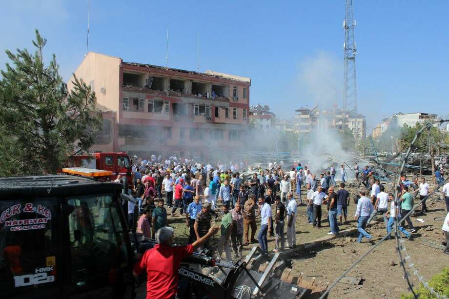 Turkish authorities and local residents stand outside a damaged building after an explosion in Elazig, eastern Turkey, on Thursday. Two car bombings targeted police stations in Turkey, killing a number of people and wounding hundreds, officials said Thursday. Photo: Kamilcan Kilic