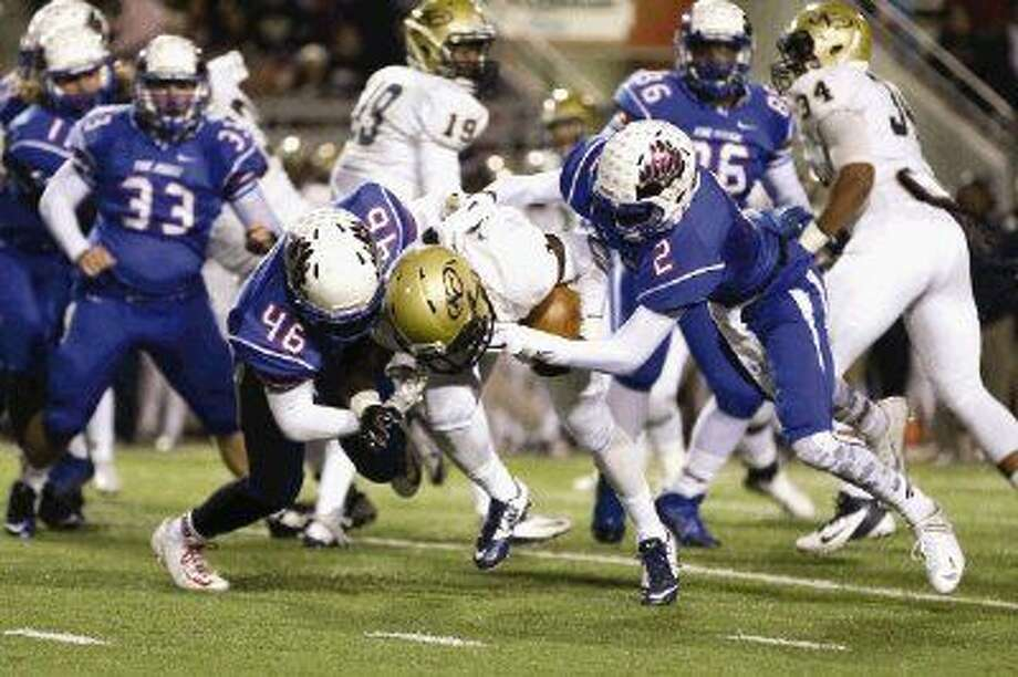 Oak Ridge's Terence Baptiste (46) and Daylon Johnson bring down Klein Collins' Zuriel Kirkwood during a Class 6A bi-district playoff game on Friday at Woodforest Bank Stadium in Shenandoah. To view or purchase this photo and others like it, visit HCNpics.com. Photo: Michael Minasi