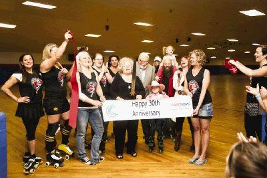 Owners, supporters and roller derby teammates celebrate after cutting the ribbon for the 30th anniversary celebration on Saturday at the Rainbow Roller Rink. To view more photos from the celebration, go to HCNPics.com. Photo: Michael Minasi