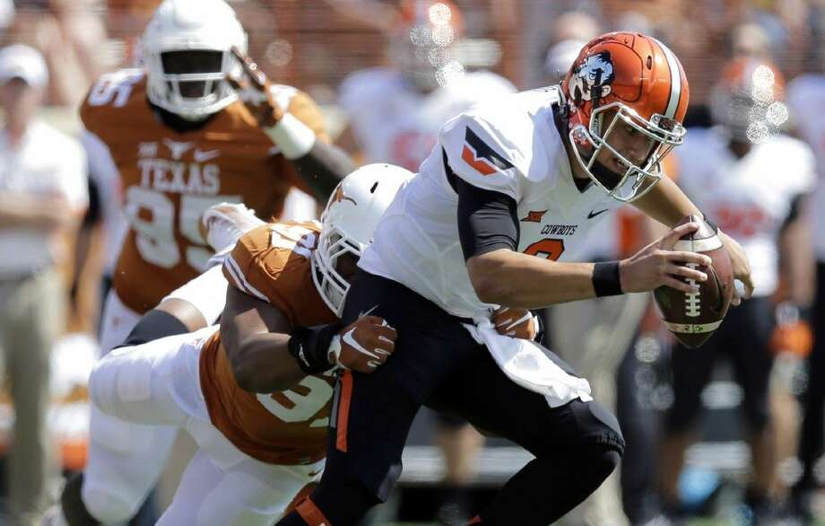 Oklahoma State's Mason Rudolph, right, is pressured by Texas's Bryce Cottrell (91) during the first half Saturday in Austin. Photo: Eric Gay