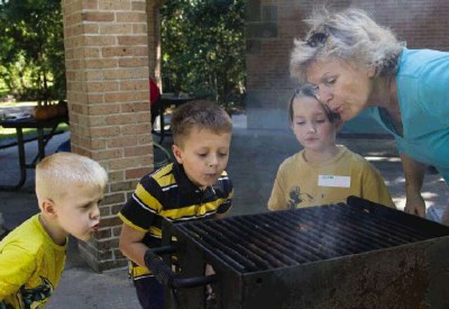 Gayle Fisher helps start a fire with Waylan and Nolan Aune and Aidan Rivers during the Special Needs Sibling meet-up Sunday at the Alden Bridge Park Pavilion in The Woodlands. Go to HCNPics.com to view and purchase this photo and others like it.