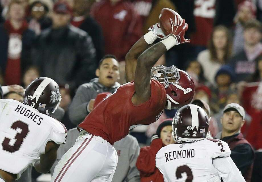 Alabama running back T.J. Yeldon catches a pass between Mississippi State defensive backs Jay Hughes and Will Redmond on Saturday in Tuscaloosa, Alabama. Photo: Brynn Anderson