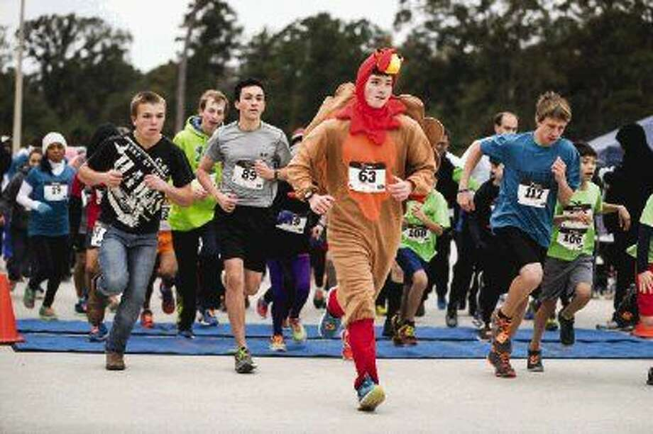 Hayden Lynch, in turkey costume, sprints from the starting line with the rest of the runners during the city of Conroe's Turkey Trot on Saturday at Carl Barton Jr. Park in Conroe. Gavin Stowe (left) also runs in his jeans and cowboy boots. Photo: Michael Minasi