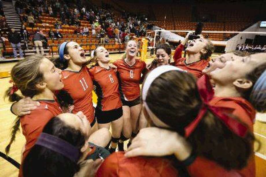The Woodlands players celebrate after earning a berth in the state volleyball tournament with a four-set victory over Richardson Pearce on Saturday in Huntsville. Photo: Michael Minasi