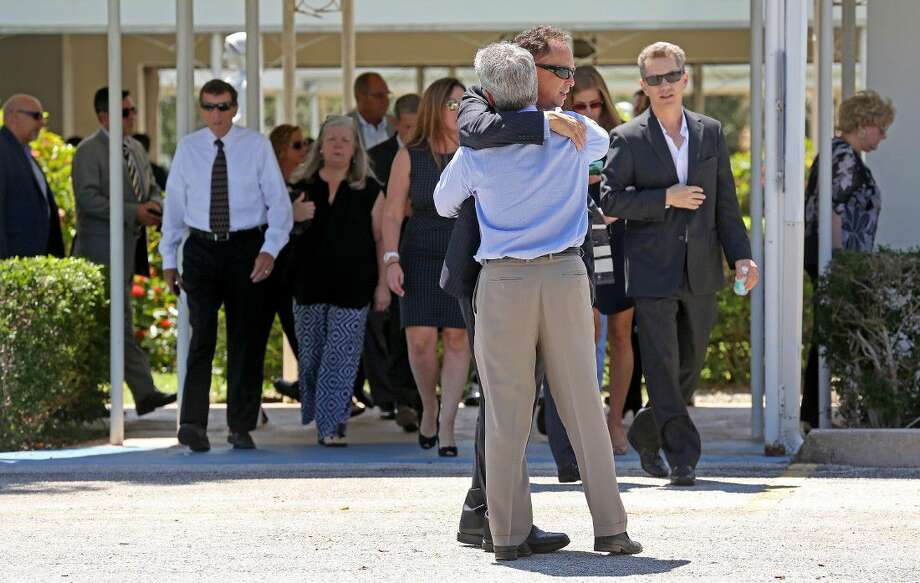 Mourners exit the Parker Playhouse following a memorial service for John Stevens and his wife Michelle Mishcon, Friday in Fort Lauderdale, Fla. Photo: Mike Stocker
