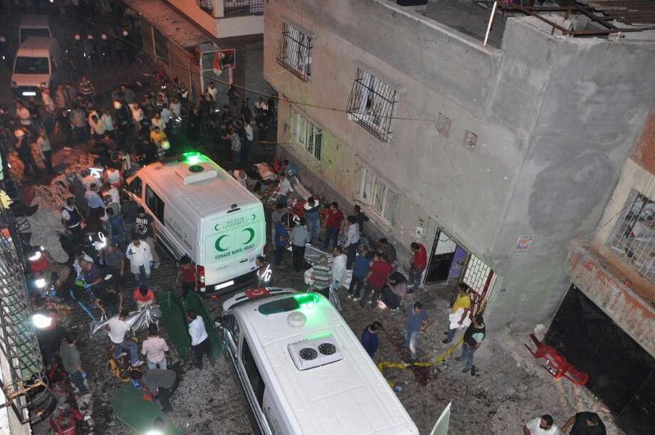People carry dead bodies into ambulances after an explosion in Gaziantep, southeastern Turkey, early Sunday. A bomb attack targeting an outdoor wedding party in southeastern Turkey killed several people and wounded dozens. Photo: Uncredited