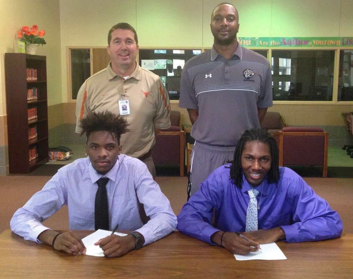 Shown here at the signing were (back row) Conroe principal Dr. Mark Weatherly and Conroe basketball coach Daryl Mason. Front row is Marcus Keyser (left) and Tremont Moore.
