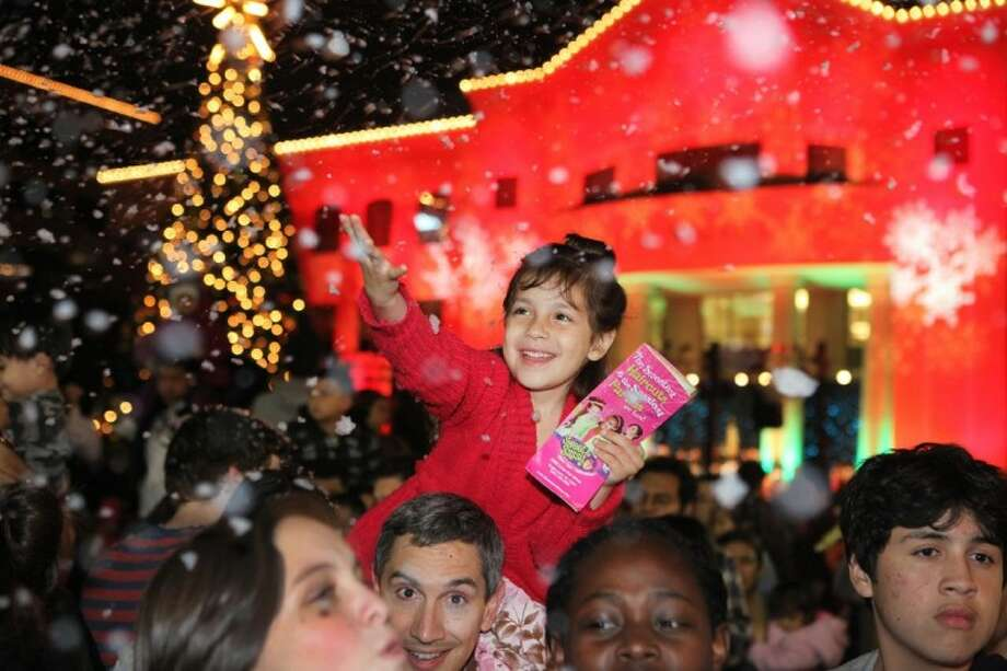 Valentina Giannone, 5. of Richmond, tries to catch fake snowflakes Thursday at the Sugar Land's 10th Annual Christmas Tree Lighting Event in Sugar Land Town Square. Photo: Photo By Alan Warren