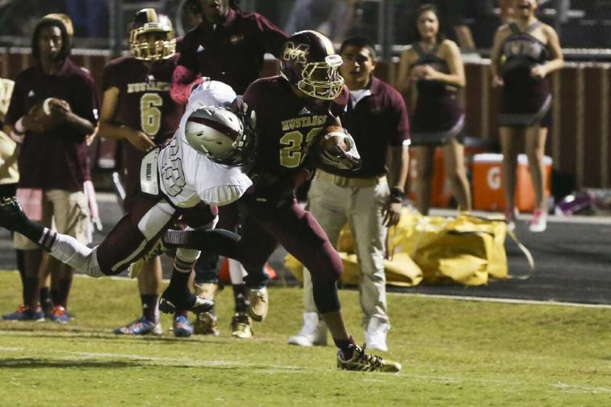 Magnolia West's Adrian Thomas tries to get past Magnolia defenders on Friday at Magnolia West High School. The Mustangs beat the Bulldogs 20-0. To view or purchase this photo and others like it, go to HCNPics.com. (Michael Minasi / HCN)