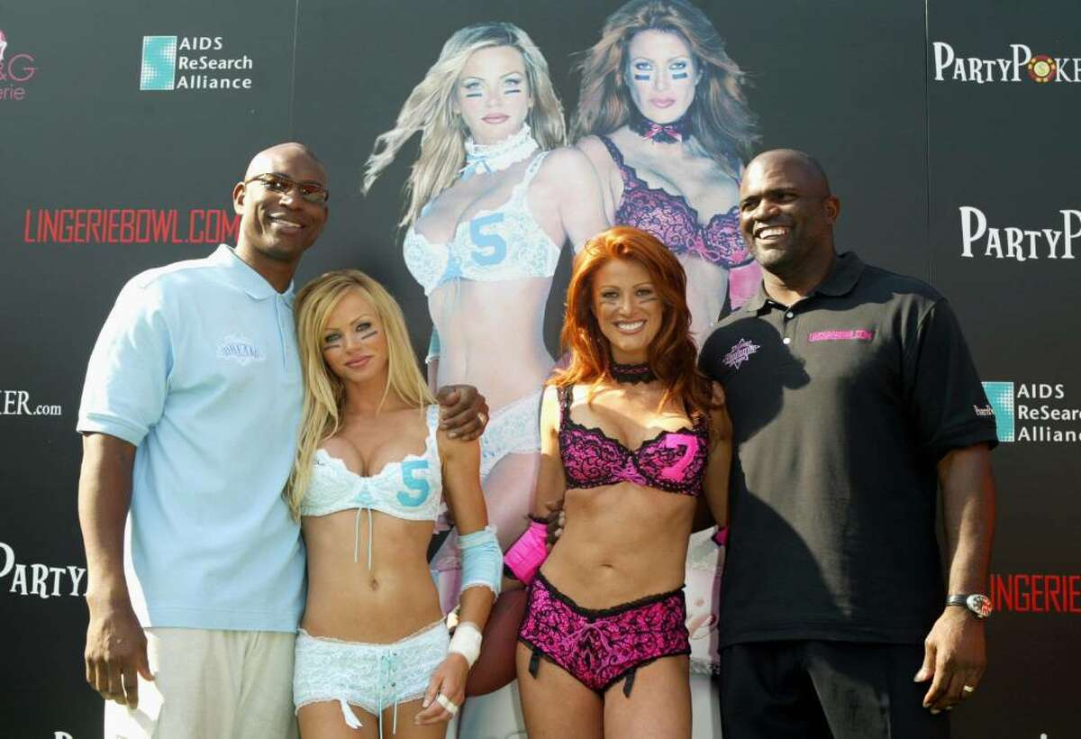 LOS ANGELES - JANUARY 26: (from left to right) Team Dream coach Eric Dickerson with his team captain Nikki Ziering, and Team Euphoria coach Lawrence Taylor poses with his team captain Angie Everhart at a news conference for the 2004 Lingerie Bowl on January 26, 2004 at the Los Angeles Coliseum, in Los Angeles, California. (Photo by Frazer Harrison/Getty Images for Lingerie Bowl)